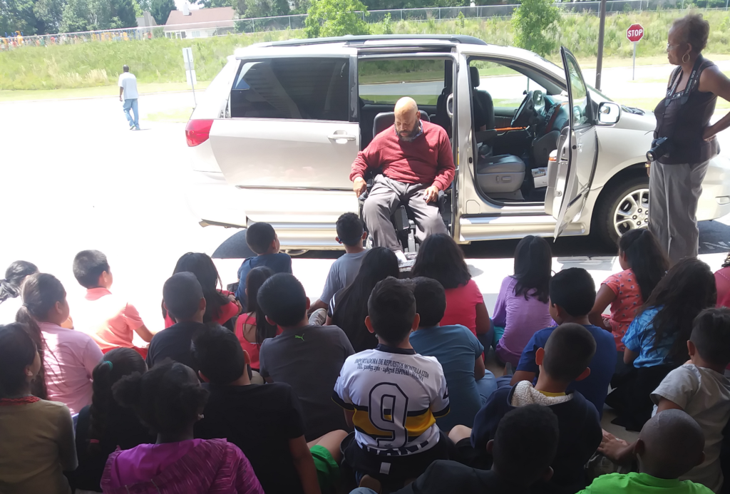 WC Harris, film maker and wheelchair user speaks to large group of children about how he can drive without the use of his legs at the Disability Awareness Career Day.