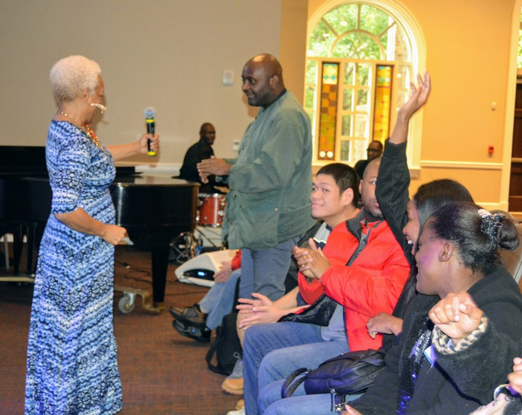 Executive Director Myrna Clayton hands microphone to audience member to all him an opportunity to sing and showcase his talent.