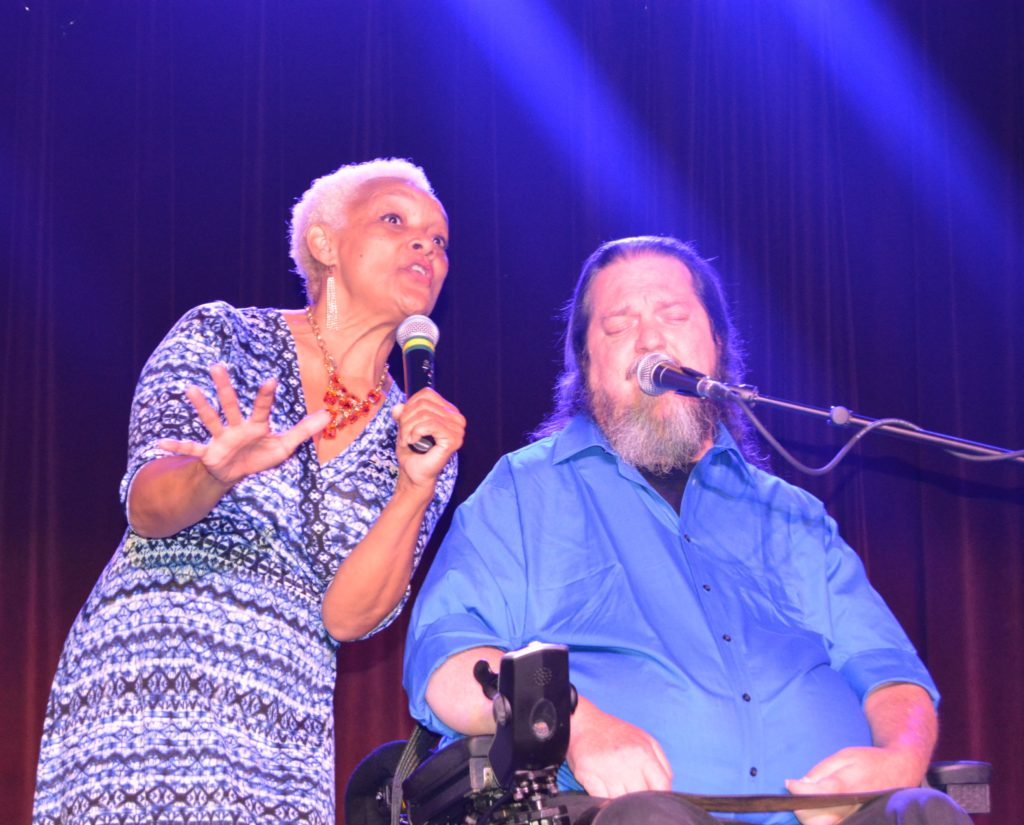 Executive Director Myrna Clayton sings on stage alongside Jazz singer Rusty Taylor (wheelchair user).