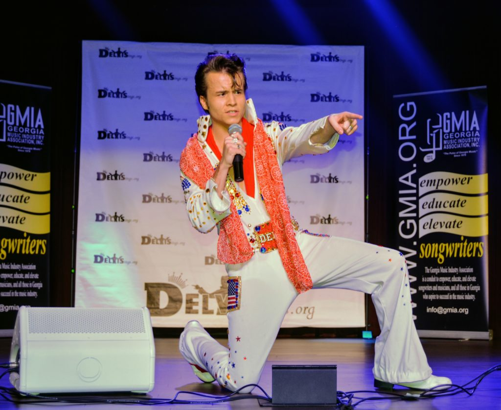 DELVIS (teen singer and Elvis Entity) gets down on one knee and points to the audience as he sings an Elvis Presley song.