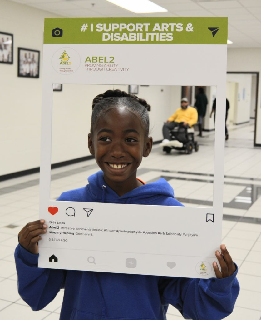Young elementary school girl poses with selfie image picture frame for at the Disability Awareness Career Day.
