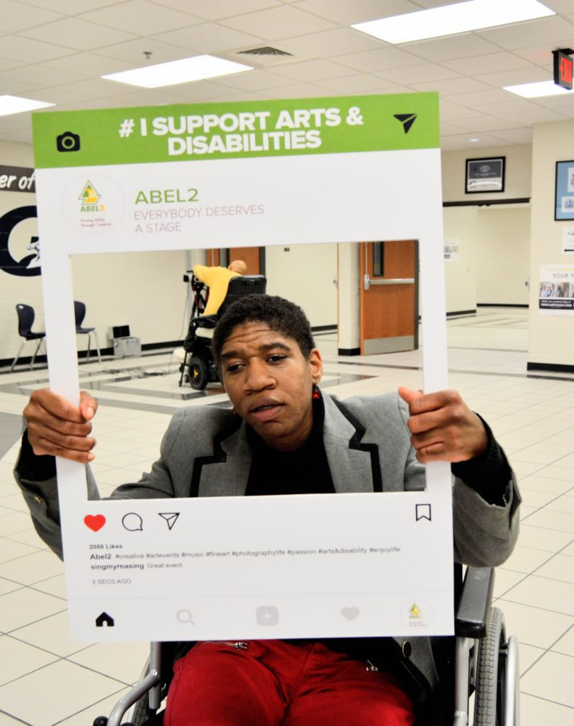 Young lady Sierra Stanley, poses with selfie image picture frame for at the Disability Awareness Career Day.