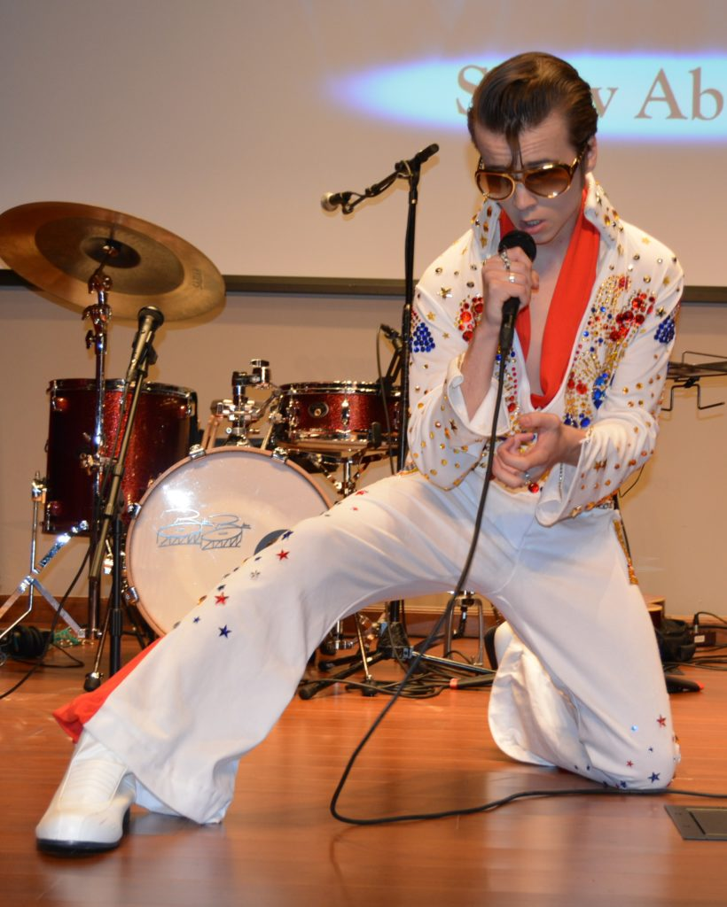 DELVIS (teen singer and Elvis Entity) wearing dark sunglasses gets down on one knee as he sings an Elvis Presley song.
