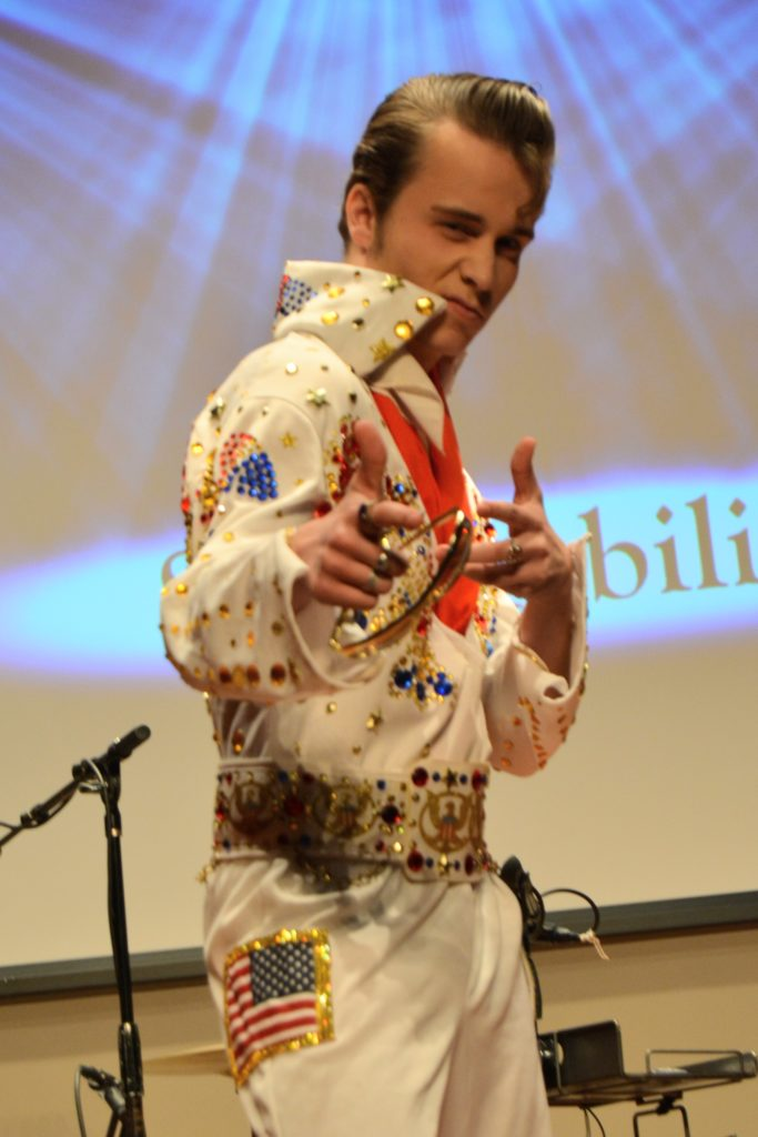 DELVIS (teen singer and Elvis Entity) poses for the camera wearing his white jumpsuit with red and blue rhinestones.