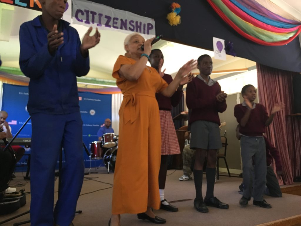 SHOWAbility Executive Director Myrna Clayton singing on stage with talented young men on the disability spectrum at a school for disabled students in Namibia south west Africa.