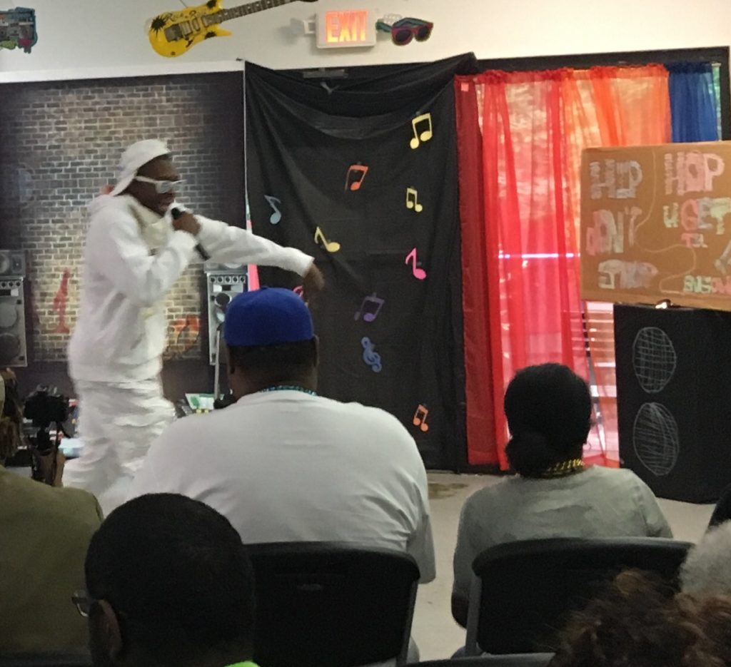 Young adult male with a developmental disability performs as a rapper with his attire matching from head to toe in all white as he entertains the audience.