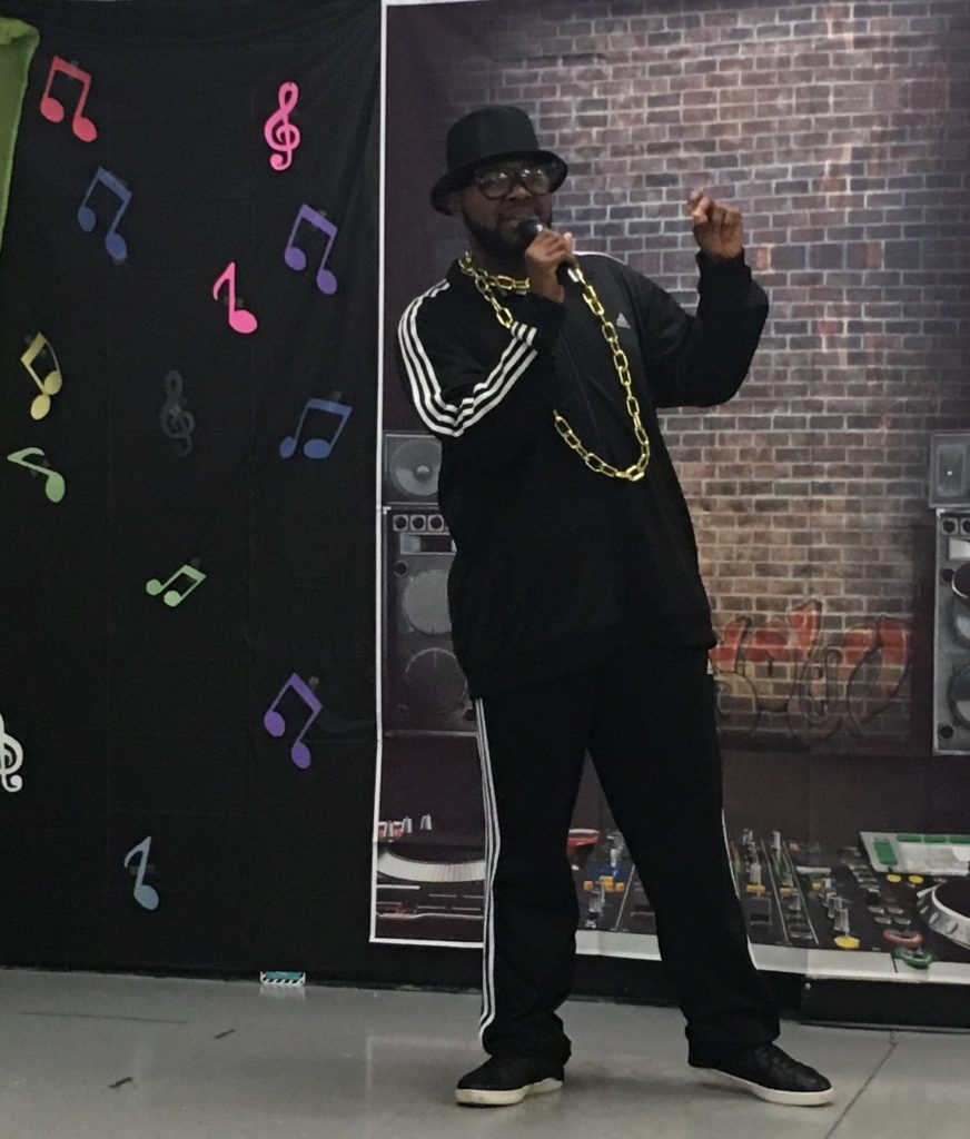Young adult male with a developmental disability wearing hip hop attire and a large gold chain performs as a rapper.