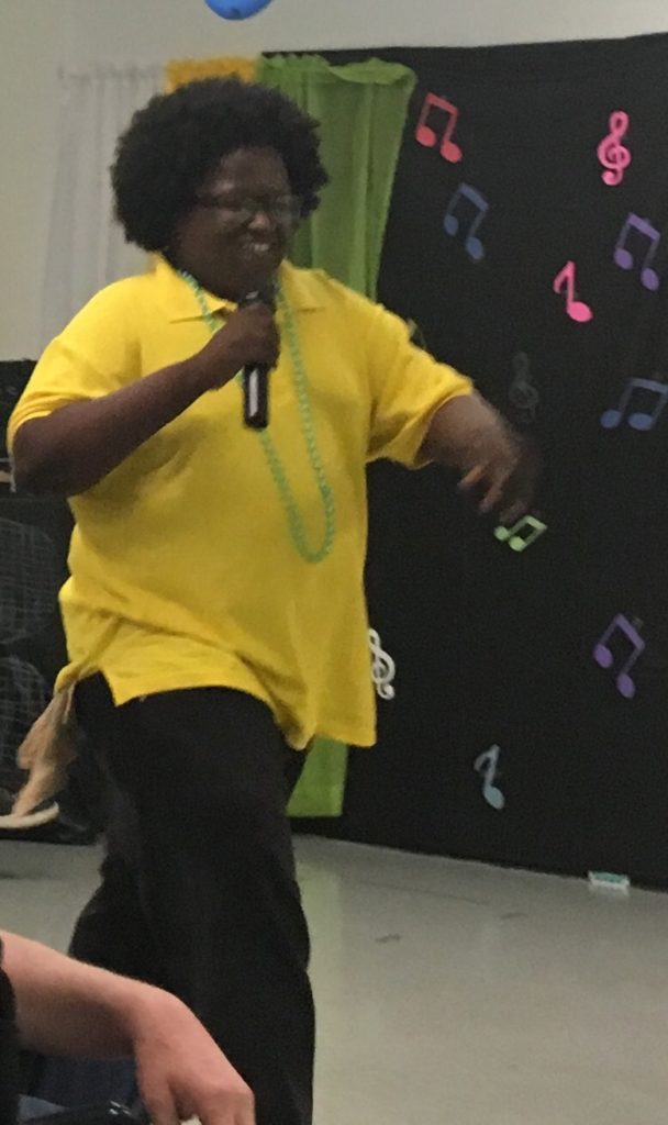 Young adult male with a developmental disability is smiling as he sings.