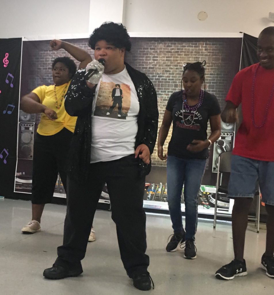 Young adult male with a developmental disability impersonates Michael Jackson for his talent. He has female dancers and one male dancer as part of his act.