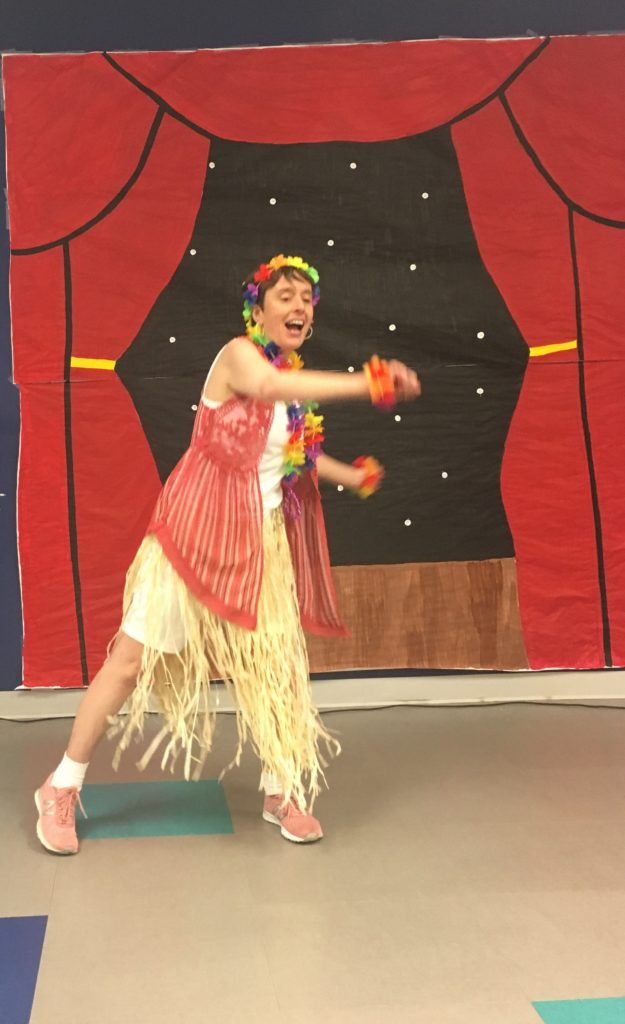 Young adult female with a developmental disability dances in a Hawaiian hula costume.