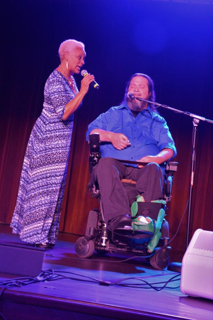 SHOWAbility Executive Director Myrna Clayton sings duet with wheelchair user, Rusty Taylor.