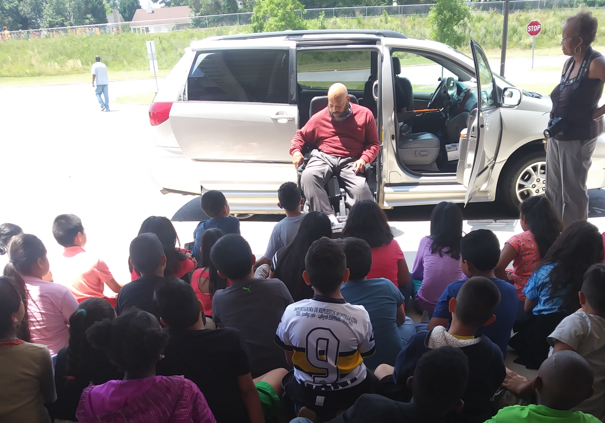 black male exiting a modified van at the curb in front of a group of seated people.